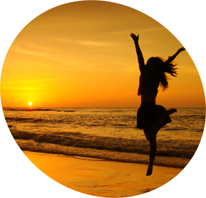 Silhouette of a young woman dancing in the beach during a sunset